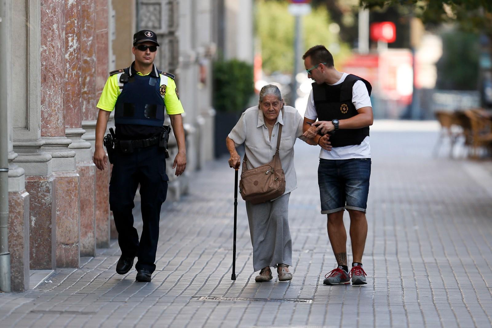 EVAKUERER: Politimenn hjelper en eldre kvinne ut av området som evakueres etter angrepet torsdag ettermiddag.