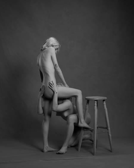 En blond kvinne står med et bein på en krakk, men en annen blond kvinne sitter på kne og simulerer oralsex på hun andre. Begge er nakne. Kjønnsorganene er ikke synlige.