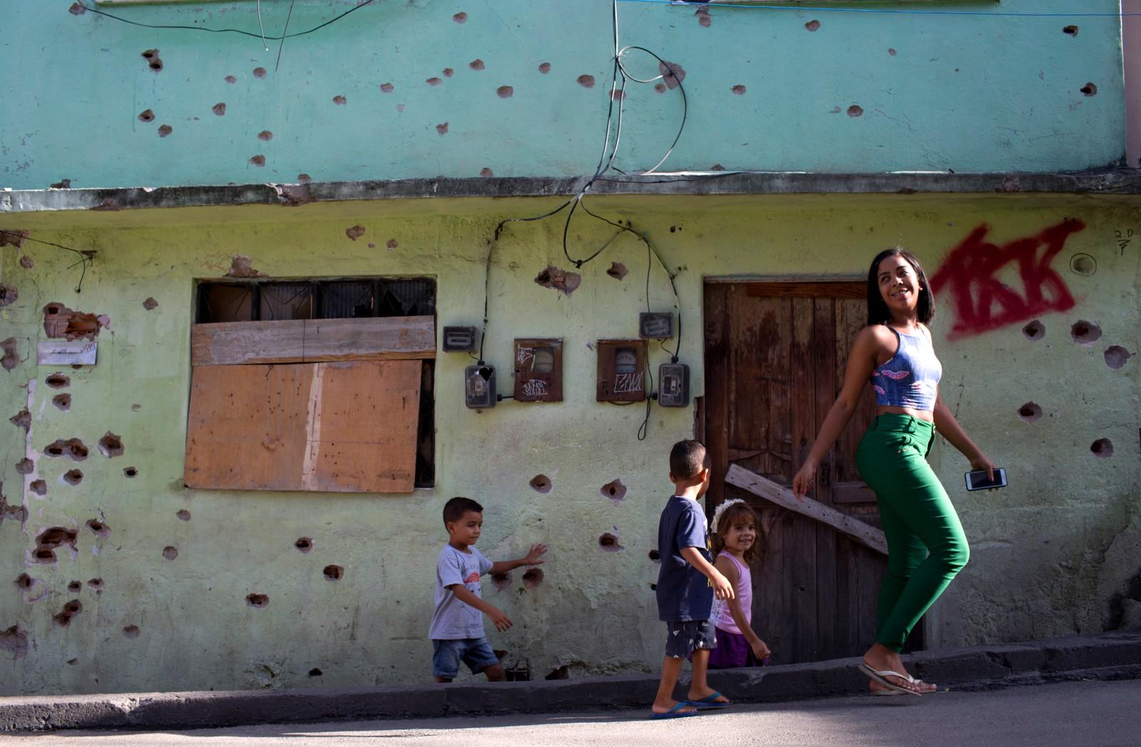 En kvinne og tre barn i favelaen Complexo de Aleamo i Rio de Janeiro, Brasil. På veggen bak ser vi kulehull etter kamper mellom politi og gjengmedlemmer.