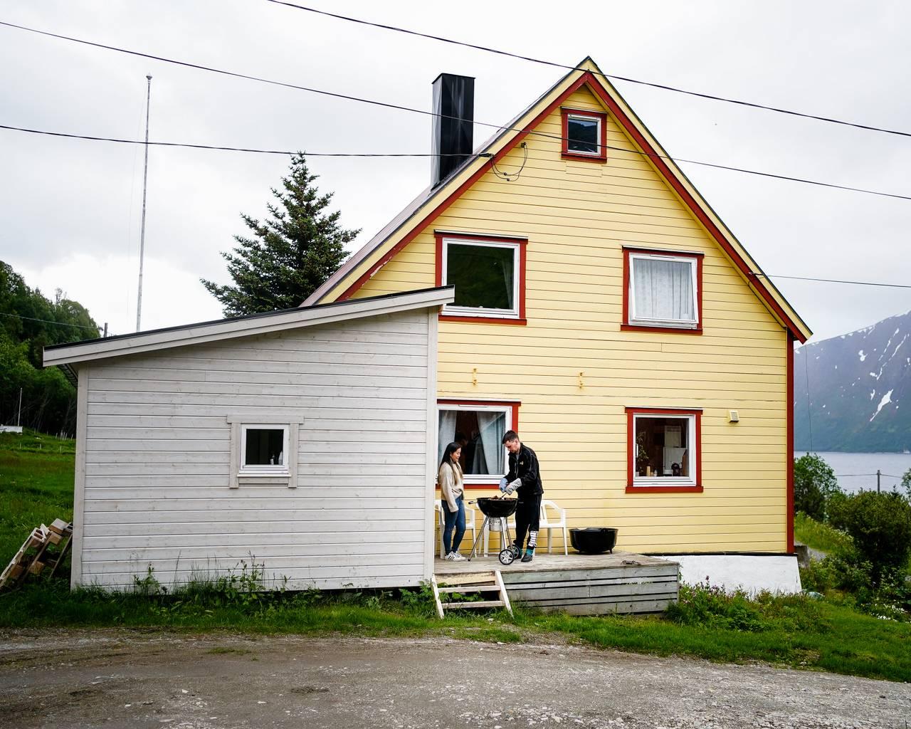 Ann-Hilde og Christian står utenfor huset sitt og griller. Huset er gult og hvitt.