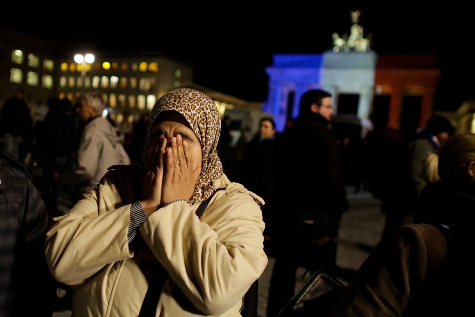 En dame utenfor Brandenburger Tor i Berlin uttrykker sorg og fortvilelse etter de tragiske hendelsene i Paris.