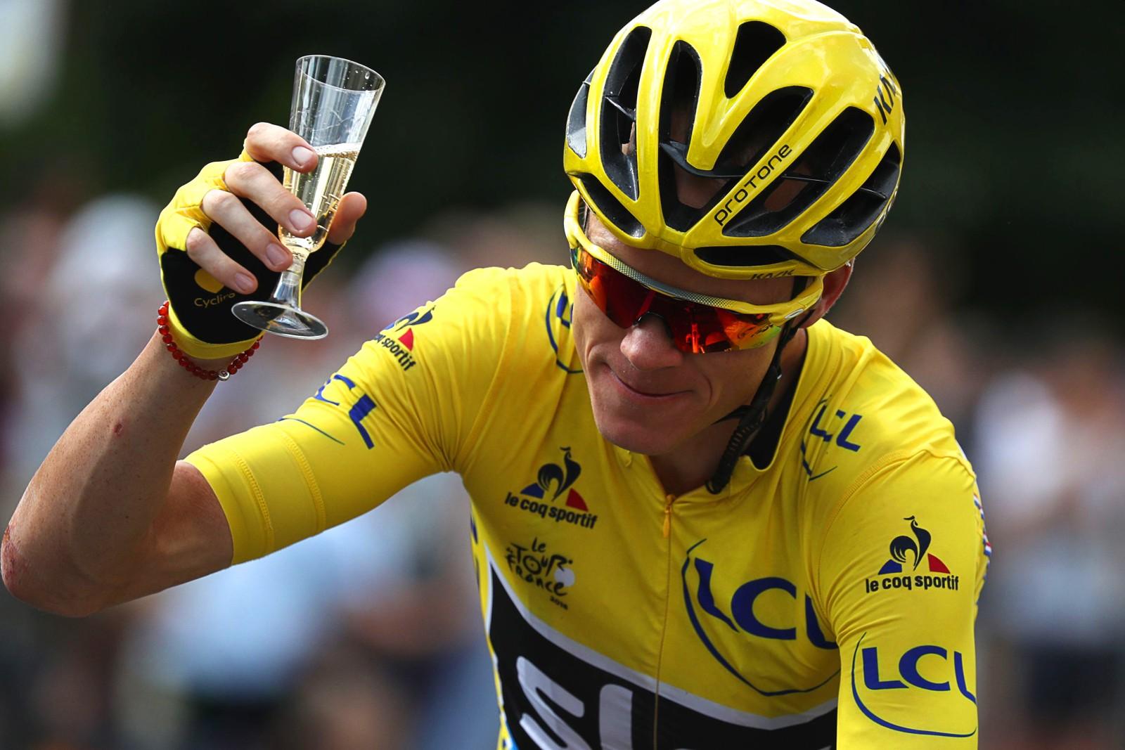 Storbritannias Christopher Froome feier seieren på forskudd med et glass champagne på sykkelen under den siste etappen av Tour de France den 24. juli.