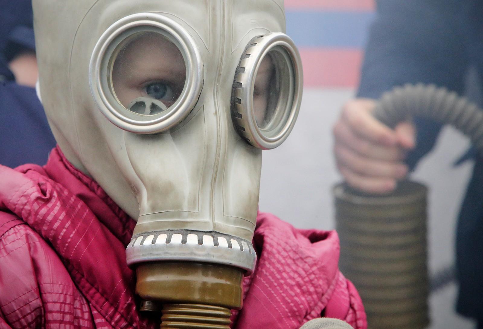 En russisk jente med gassmaske på vei ut av et røykfullt telt under en messe som ble arrangert av det russiske sivilforsvaret denne uka.