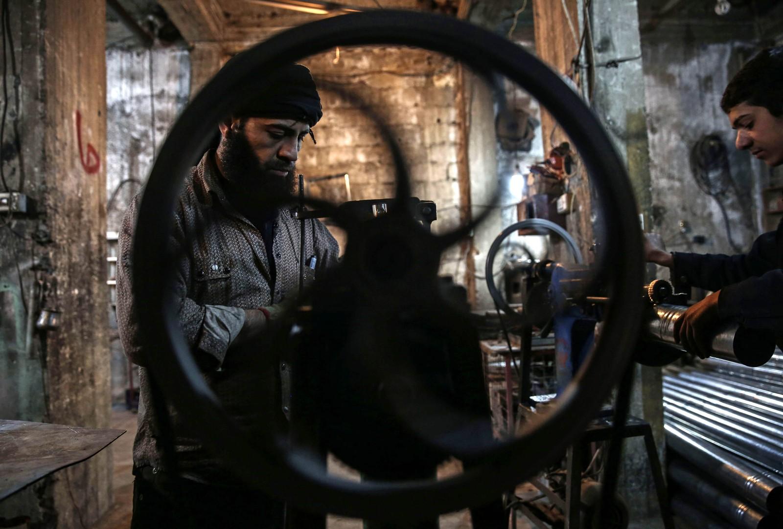 Syrere arbeider på en fabrikk i Douma hvor de lager vedovner.
