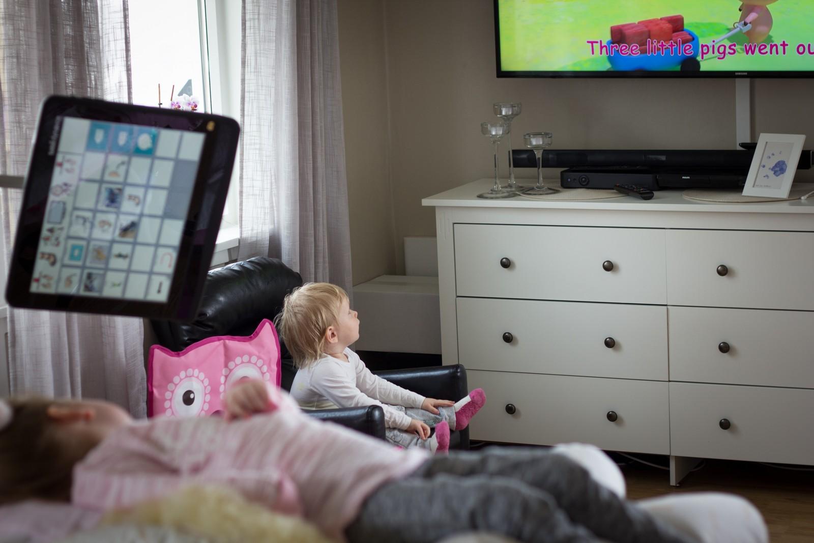 Søstrene Frida Marie (3) og Amalie (16 måneder) er hjemme i stua og ser på TV. Frida Marie ligger på en seng, mens Amalie sitter i en stol.