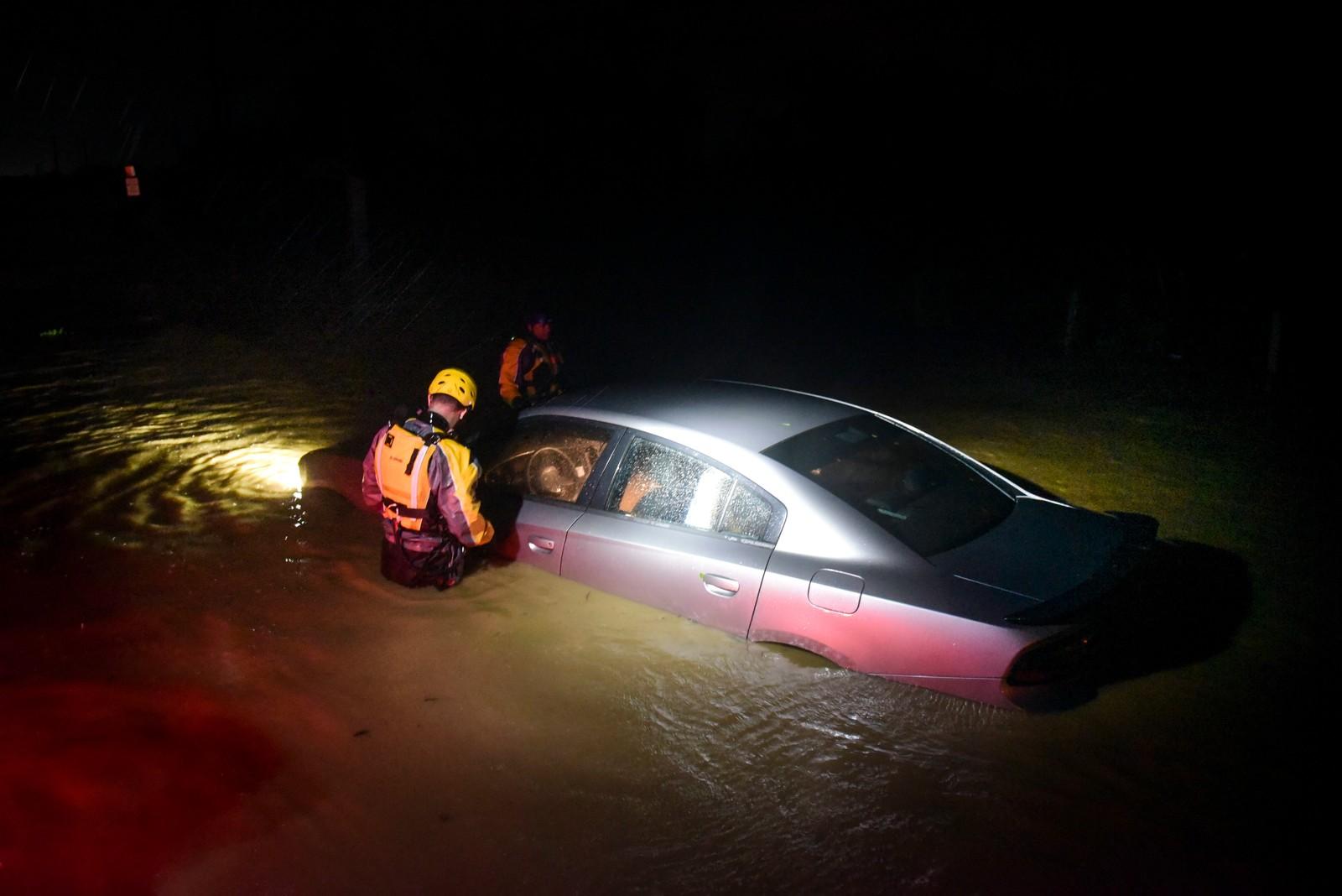 Redningsmannskaper undersøker en oversvømt bil på øya Fajardo i Puerto Rico.