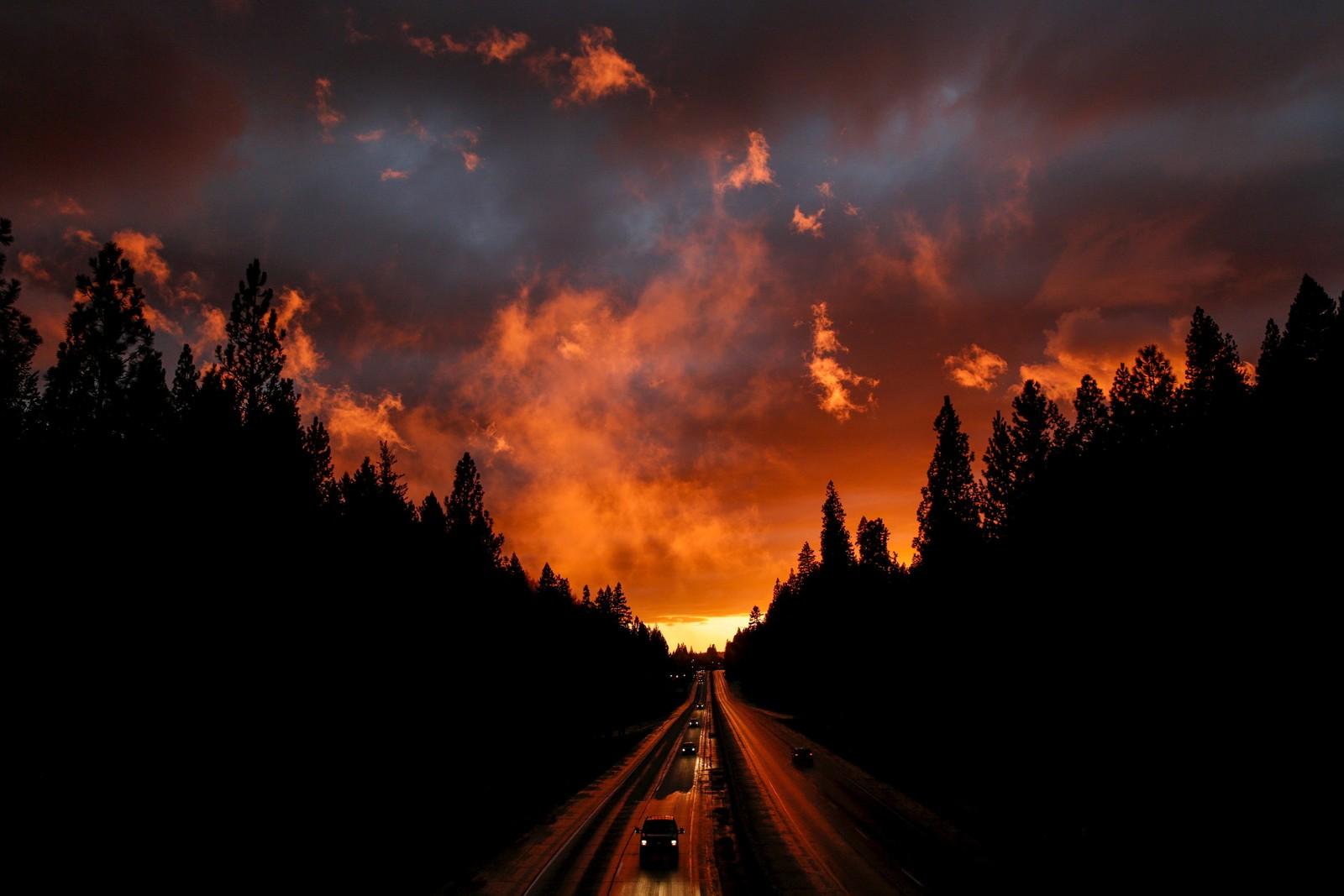 En vinterstorm bader i sterke farger fra solnedgangen over motorvei I-80 nær Baxter i California.