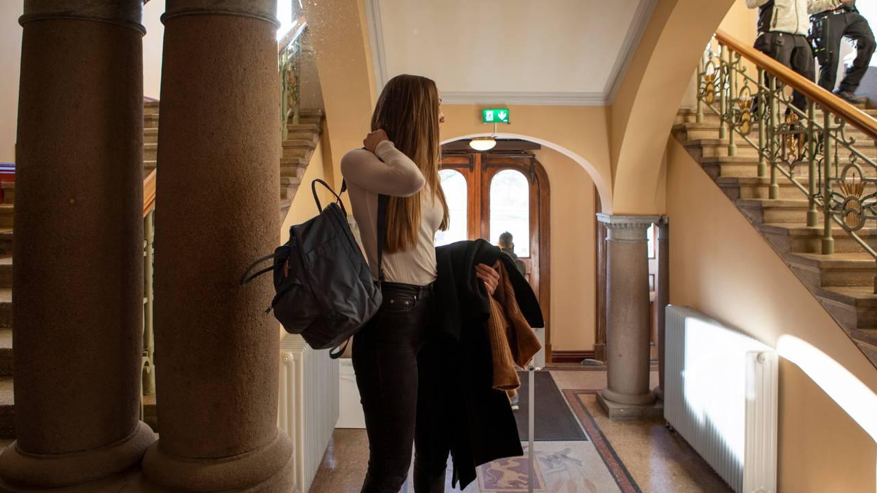 Ingvild Dagsland står innenfor hovedinngangen ved et bygg på NMBU i Ås. Store søyler fra det gamle bygget rammer inn bildet. Hun har en sekk på ryggen og kåpe i hånda. Hun snur seg vekk. I trappa ser man studenter på vei ned.