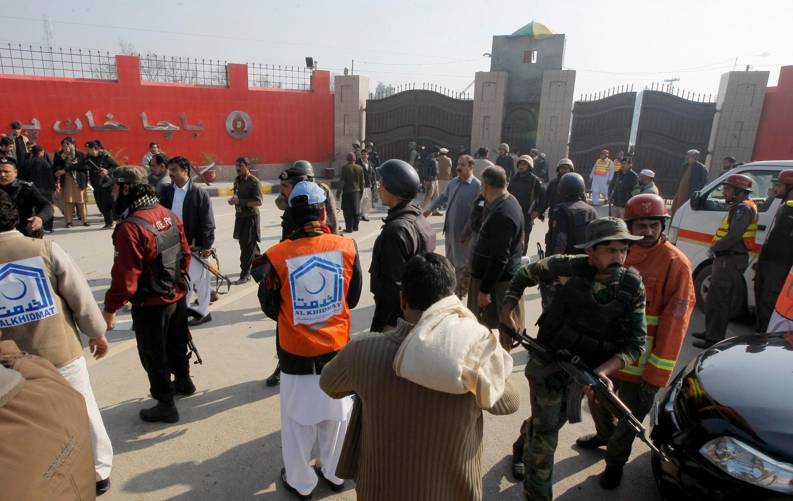 Soldater og hjelpearbeidere ved hovedporten til Bacha Khan-universitetet i Chasadda