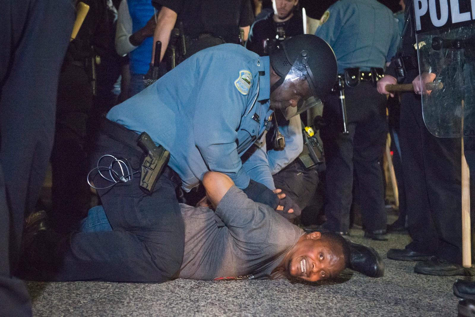 Politiet arresterer en demonstrant før skuddene ble avfyrt. Store folkemengder tok til gatene da politimesteren i Ferguson trakk seg etter langvarig press og rasismeanklager. REUTERS/Kate Munsch.