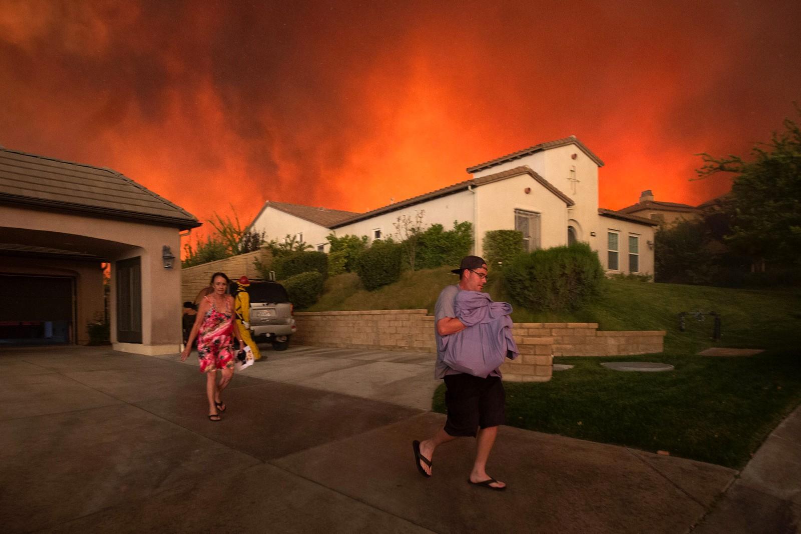 """Mennesker flykter fra hjemmet sitt under skogbrannen som ble kalt """"Sand Fire i USA. Nesten 155 kvadratkilometer sto i brann da det var på det verste. Bildet er tatt nær Santa Clarita i California den 23. juli."""