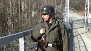Utkledt tysk soldat vokter broen over juvet