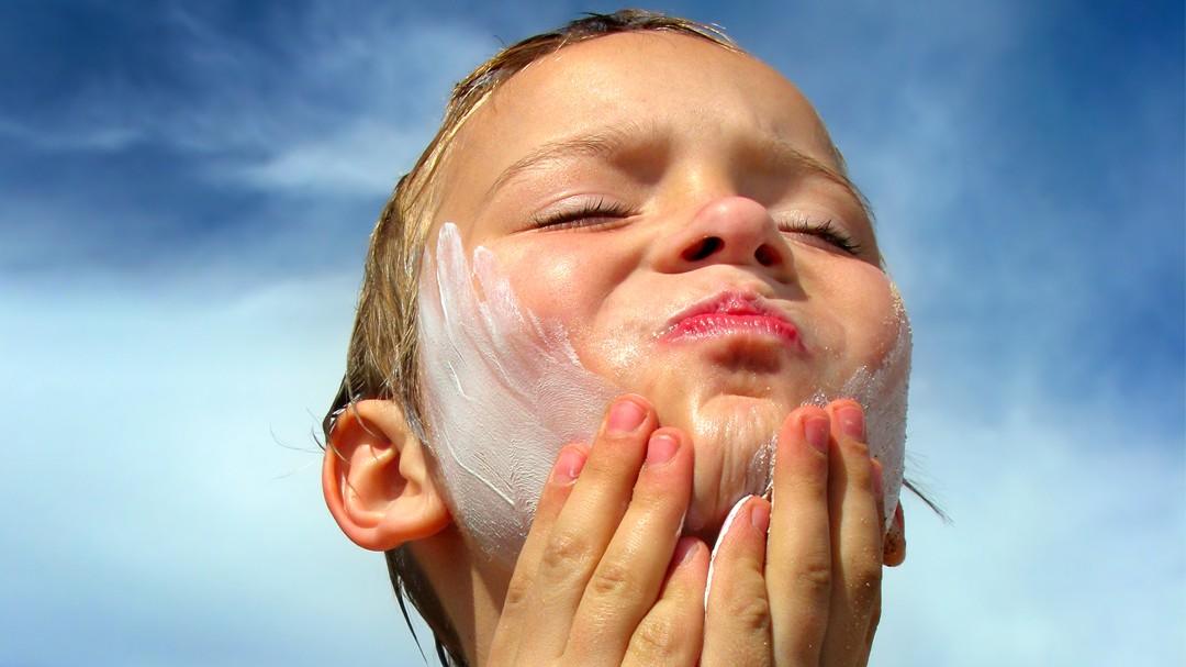 Gutt smører seg med solkrem