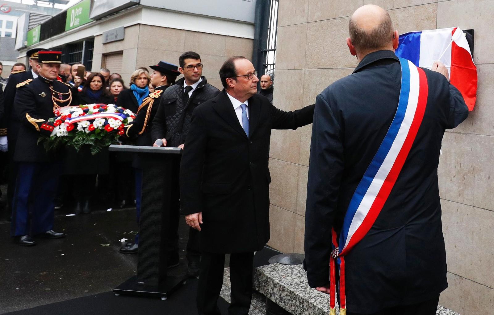 President Francois Hollande og ordføreren i kommunen Saint-Denis, Didier Paillard, avduket en minneplakett utenfor fotballarenaen Stade de France søndag, der det første offeret for terrorangrepet 13. november 2015 ble drept.