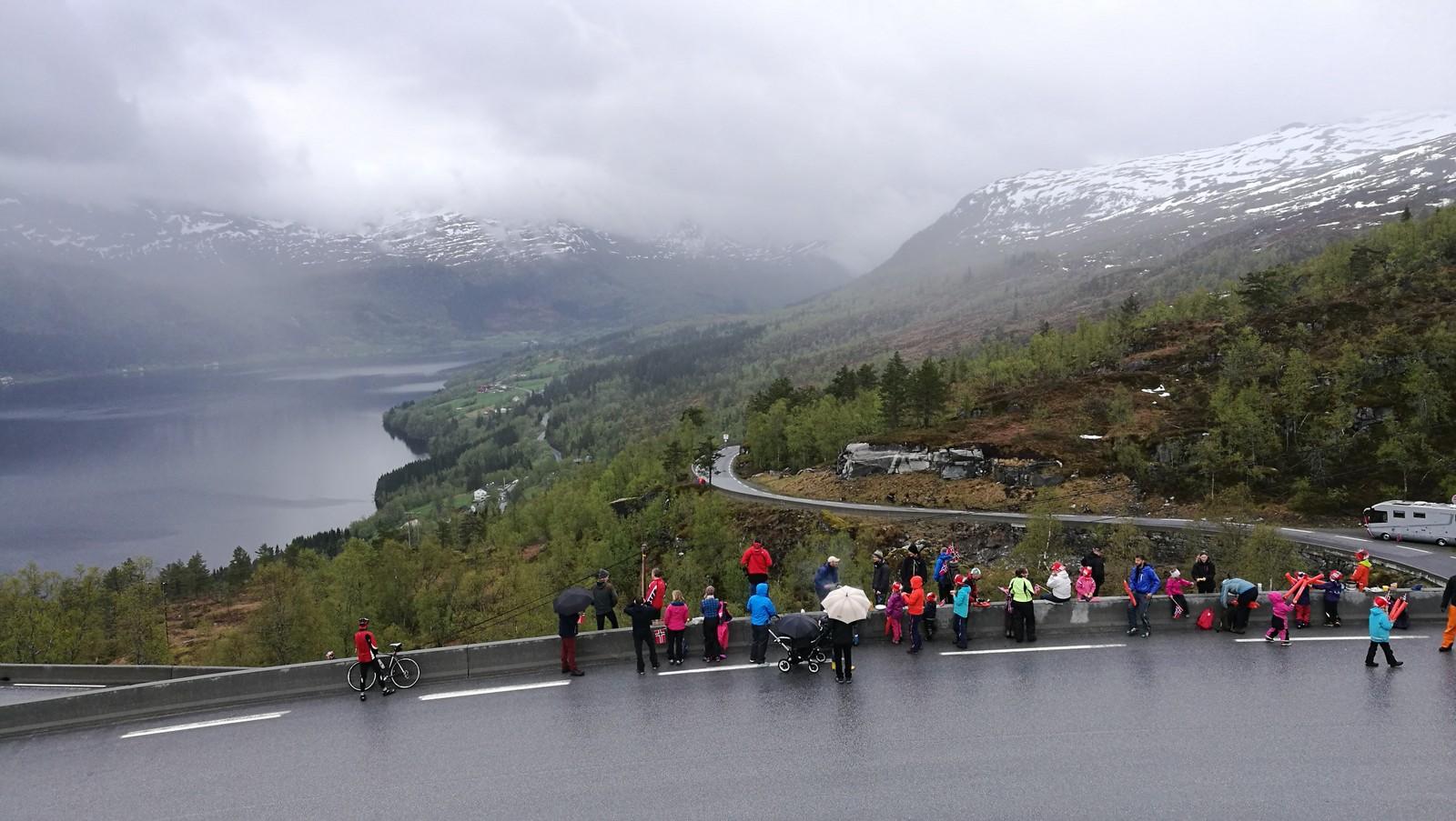 Folk står langs vegkanten for å få med seg at 120 proffsyklistar klatrar oppover dei bratte svingane på Røyrvikfjellet.