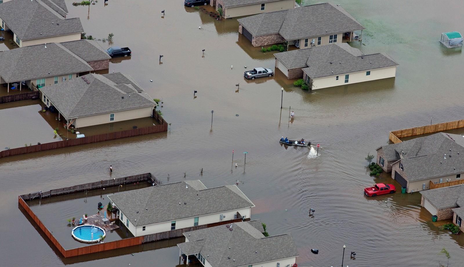 MANGE RAMMET: En båt kjører mellom flomrammede hus i Hammond, Louisiana.