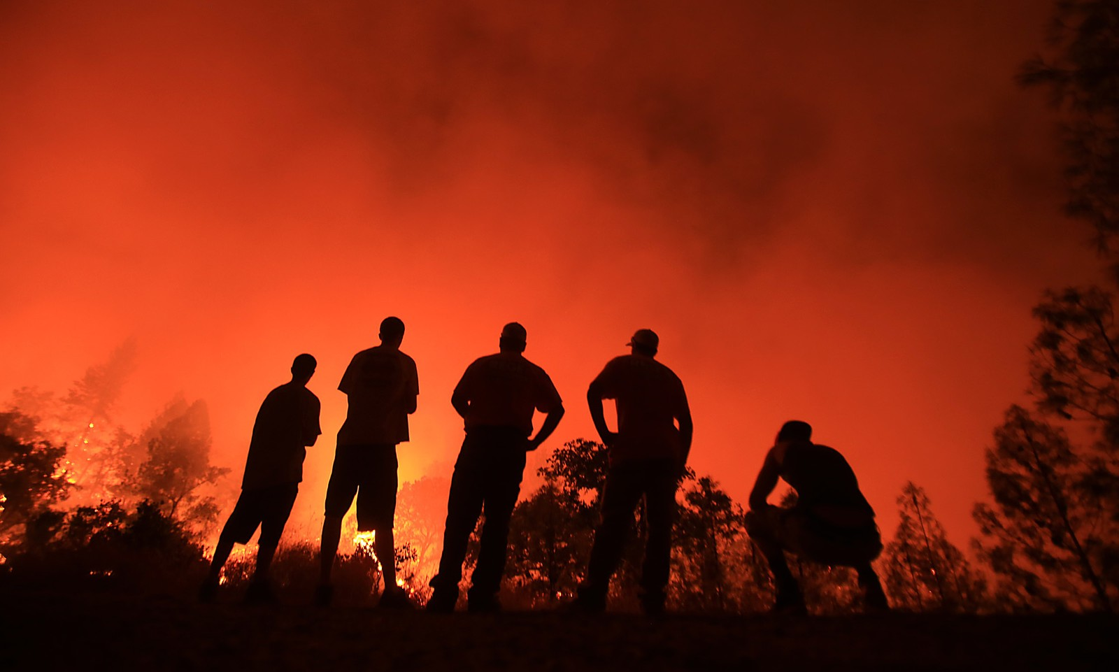 APTOPIX California Wilfires Residents watch as a wildfire burns near their homes off Morgan Valley Road in Lower Lake, Calif., Saturday Aug. 13, 2016. More evacuation orders have been issued as the wildfire grows in Northern California, threatening the lake community of about 1,300 that was evacuated a year ago because of a destructive fire. (Kent Porter/The Press Democrat via AP)