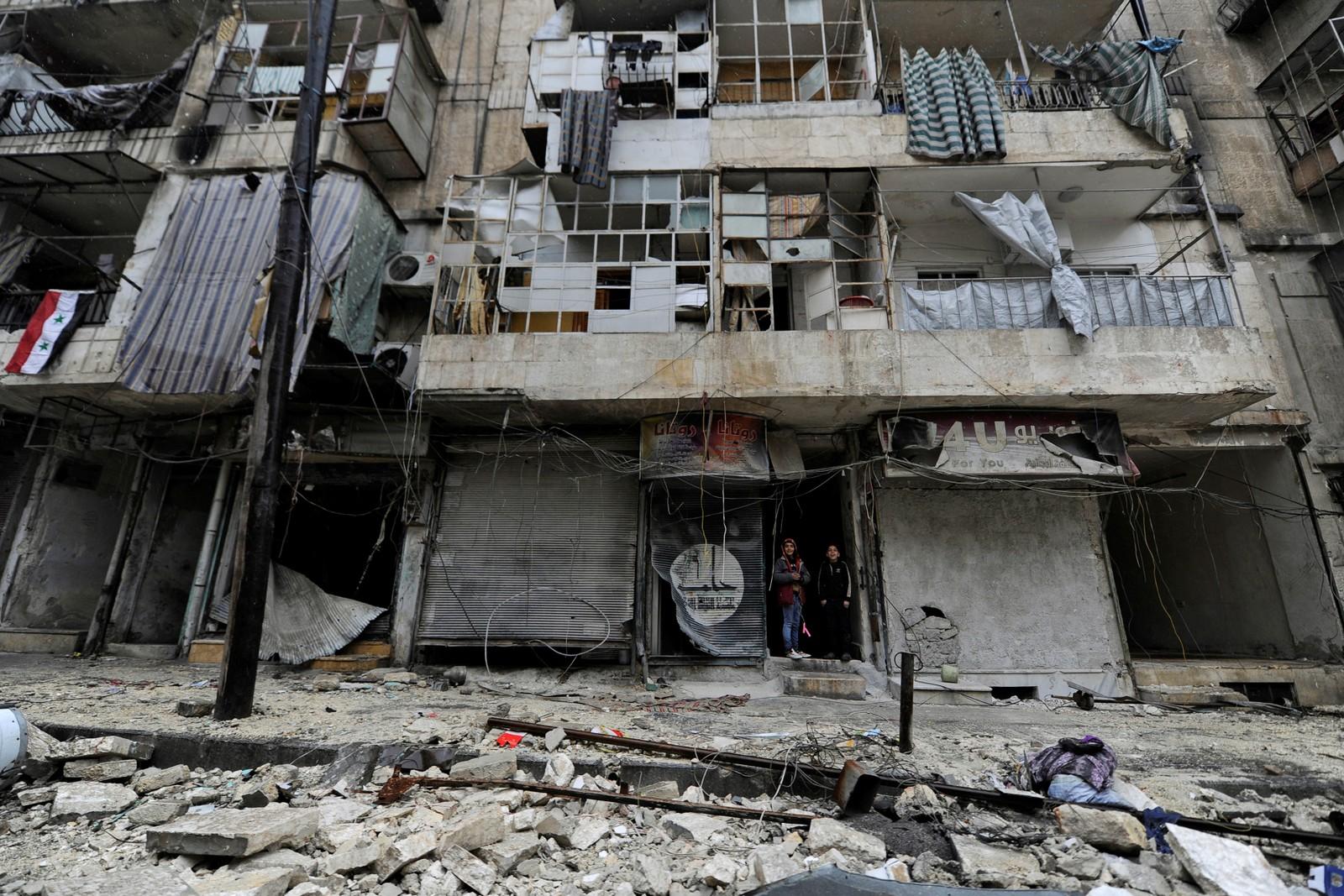 To gutter står i inngangen til en bygning ødelagt av krigens herjinger i regjeringskontrollerte al-Shaar i Aleppo.