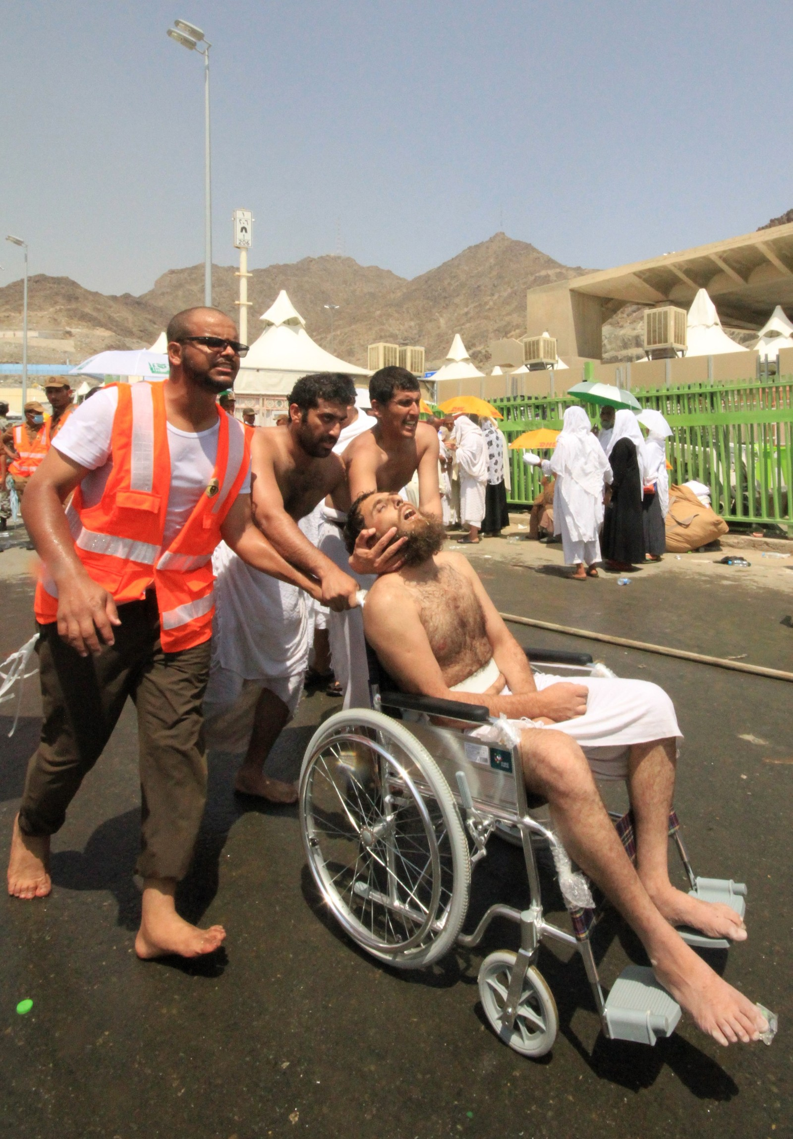 Redningspersonell frakter en skadet mann bort i rullestol fra stedet der over 700 ble trampet i hjel.