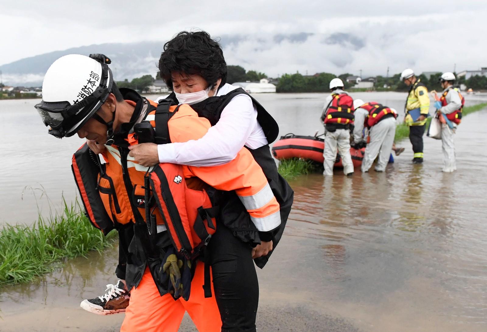 En innbygger i Asakura får hjelp av en redningsarbeider.