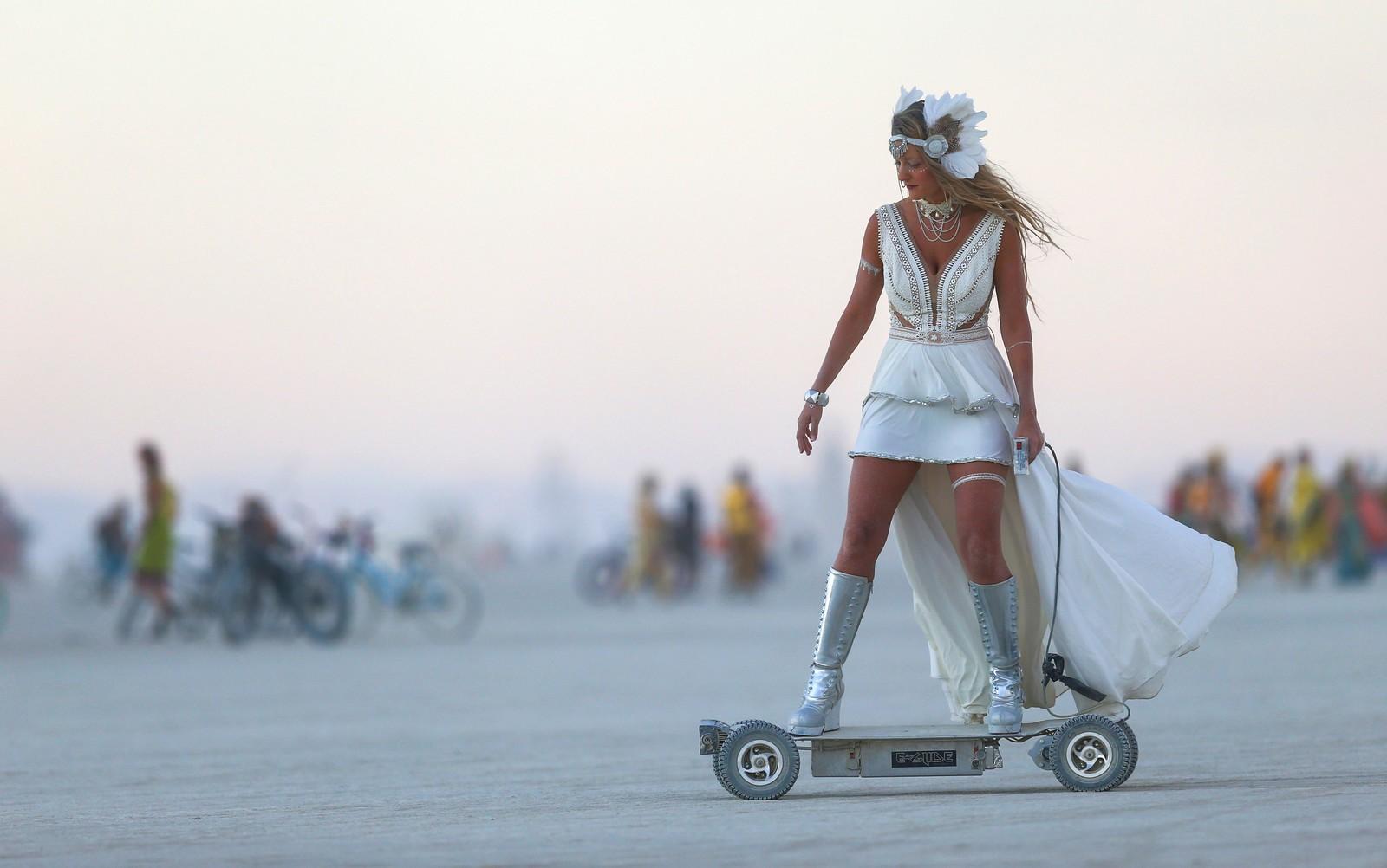 Denne kvinnen på elektrisk scooter er en av deltakerne på festivalen Burning Man i Black Rock-ørkenen i Nevada, USA. I 2015 var det 70.000 mennesker som festet en uke i ørkenen. Burning Man er en musikk- og kunstfestival. Målet er at publikum skal være selvforsynte med nesten alt, inkludert mat og drikke, og at det ikke skal være spor etter dem når festivalen er ferdig. Bildet er tatt 31. august.