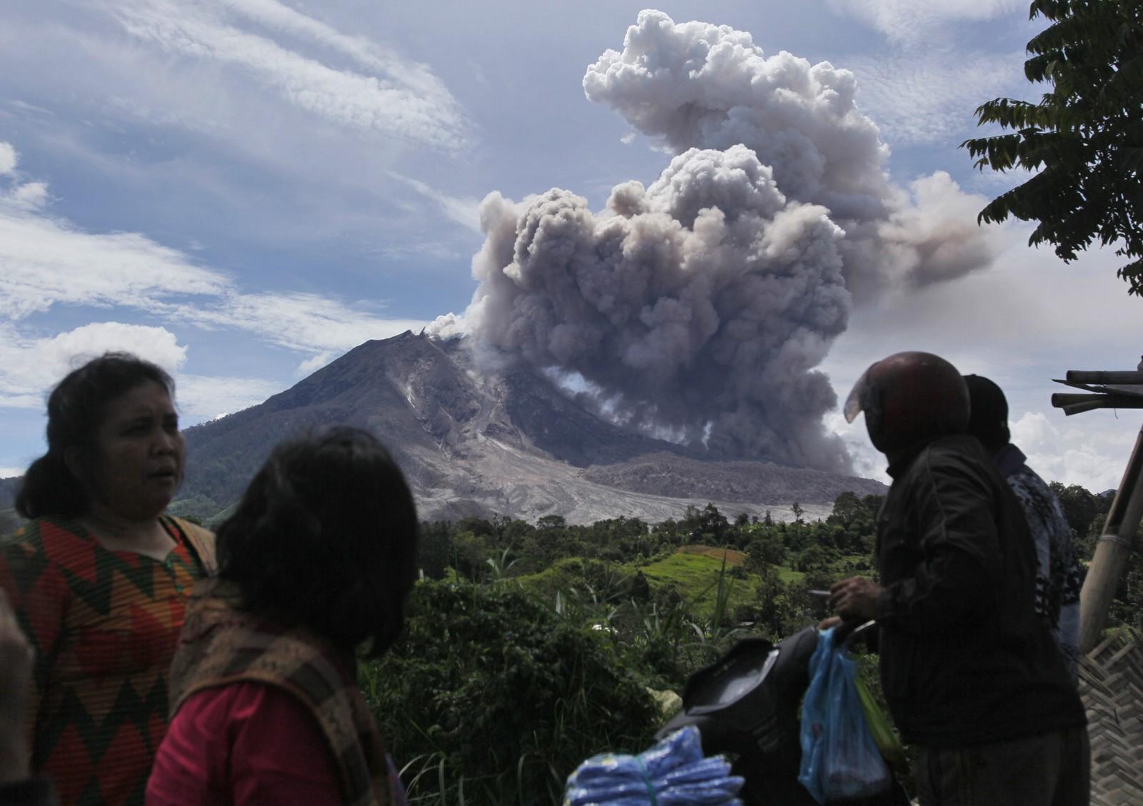 Folk i landsbyen ser på skyen. Frykten er stor for et større utbrudd.