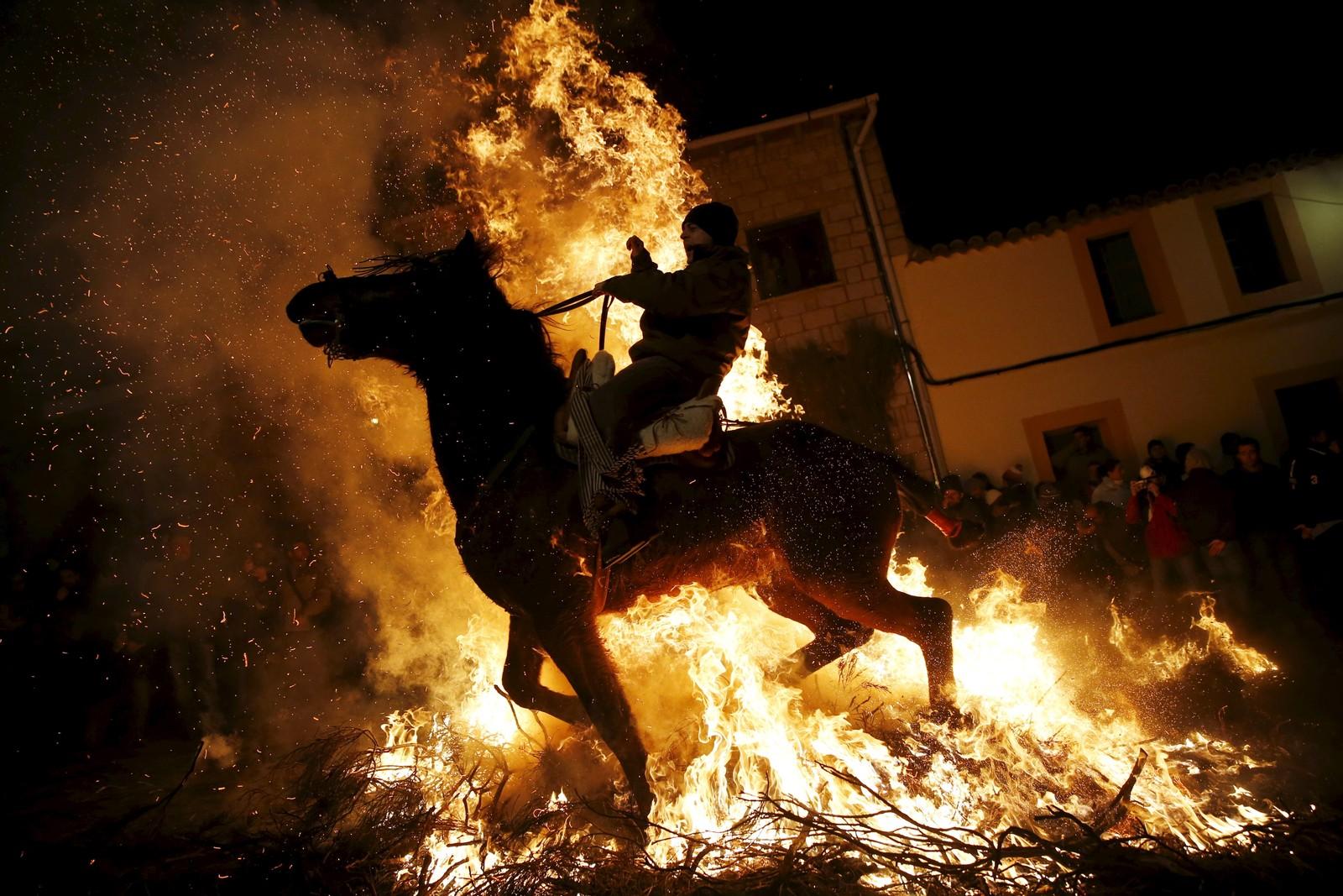 En mann rir gjenom et flammehav under den årlig feiringen «Luminarias» i spanske San Bartolome de Pinares.