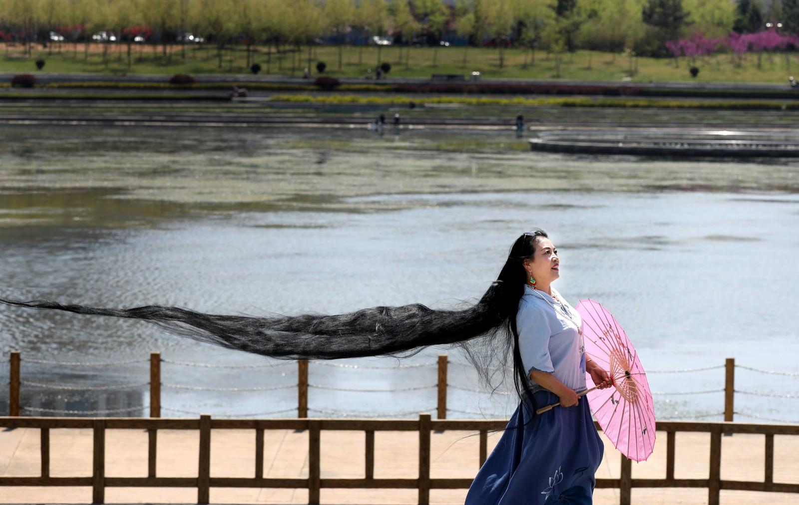 En kvinne poserer for fotografen i Weihai i Kina.