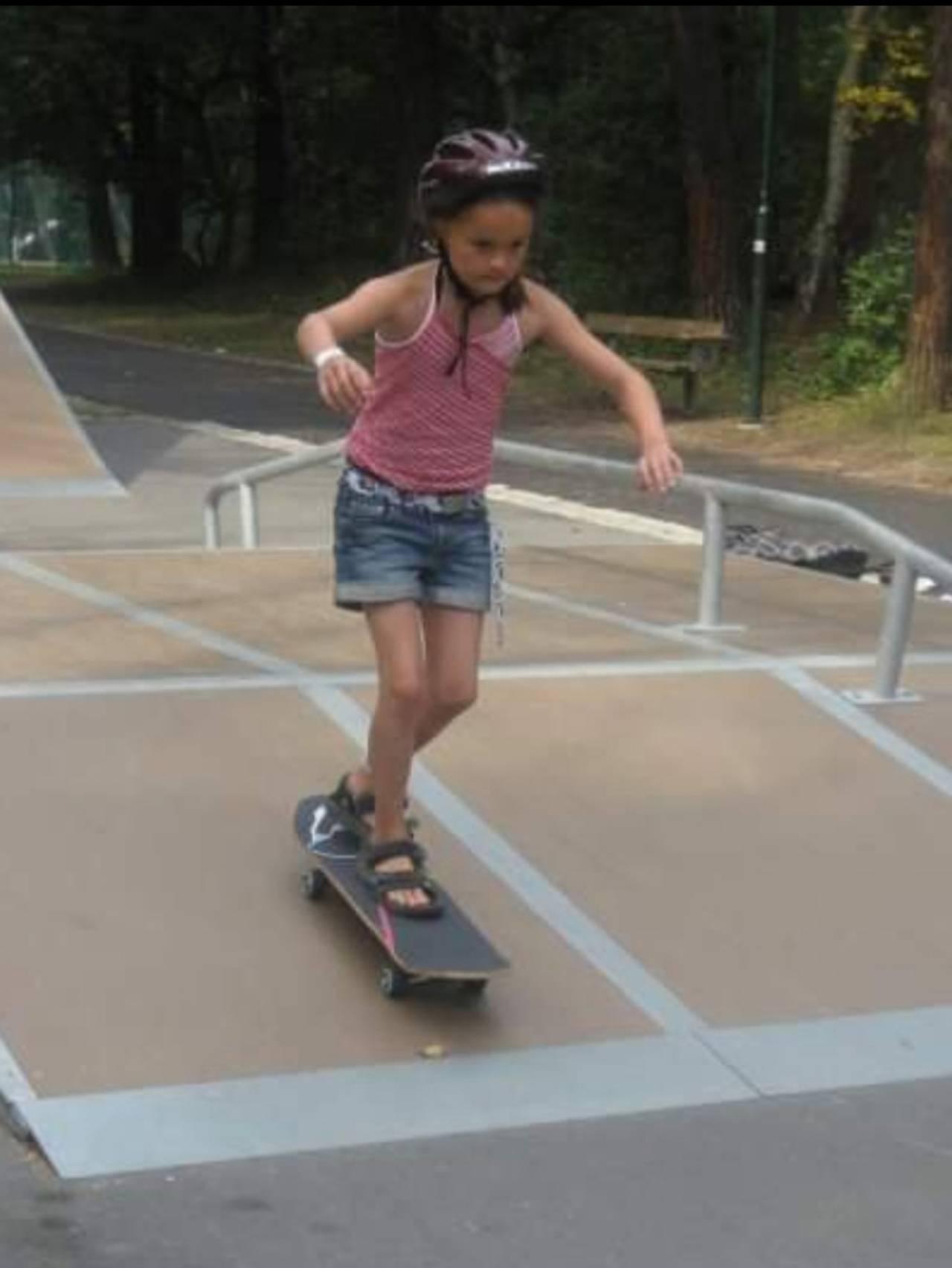 Andrine står på skateboard.