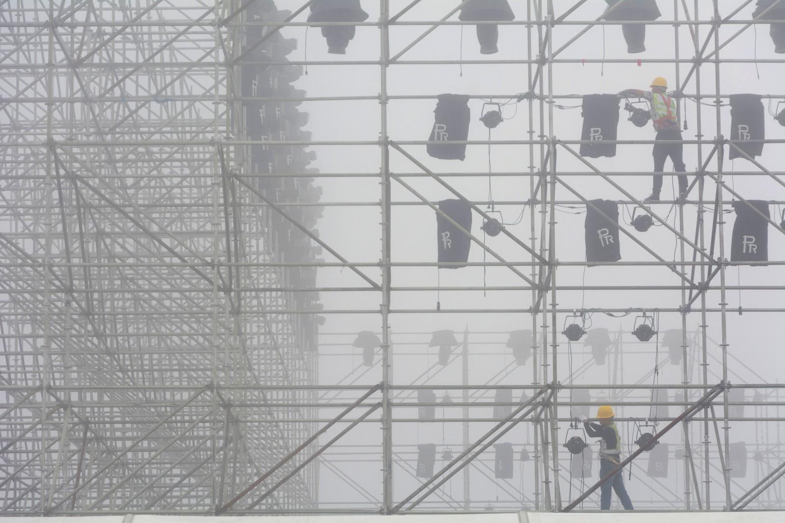 Arbeidere setter opp lyskastere før toppmøtet Verdens økonomiske forum i Dalian i Kina.