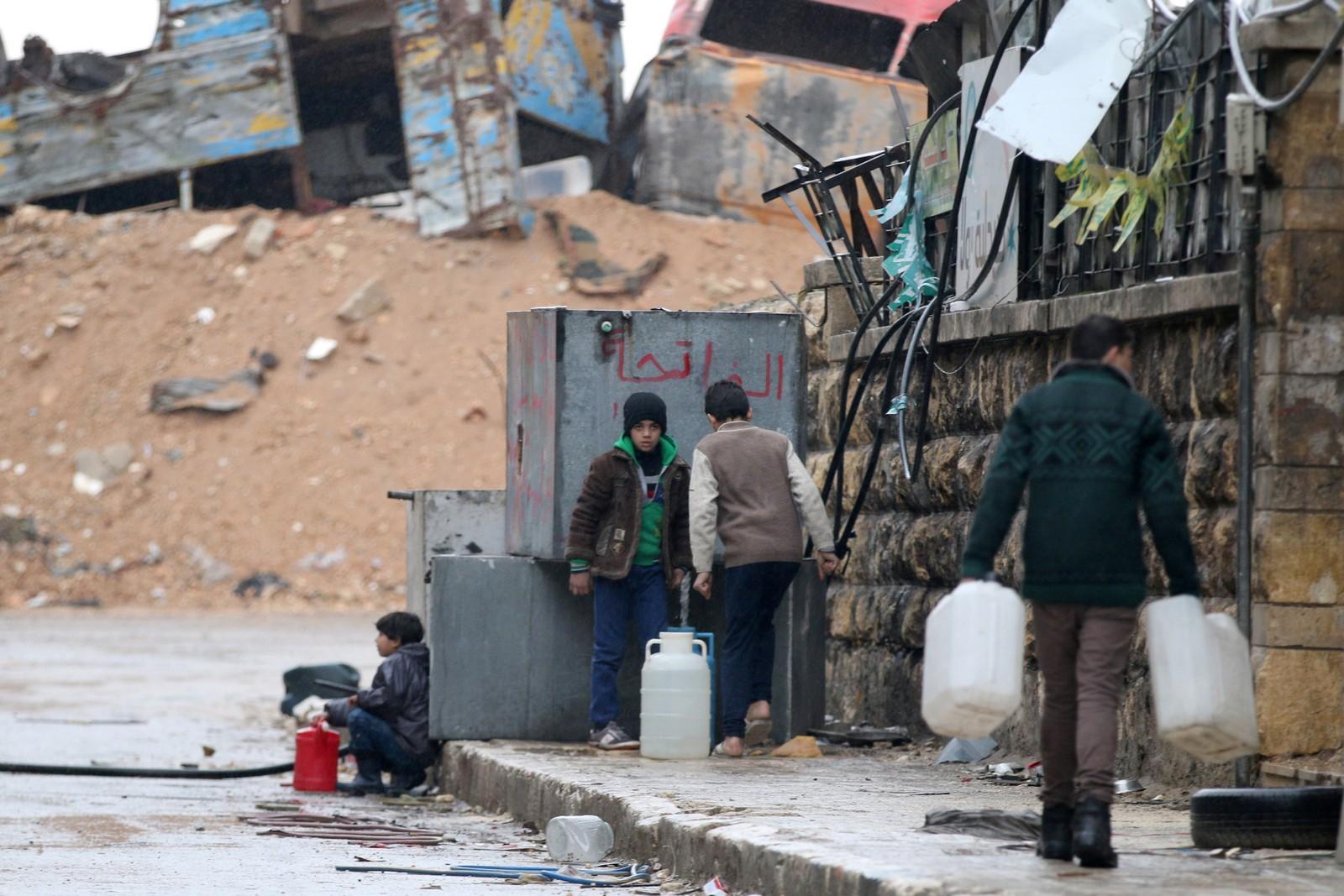 Sivile fyller vann på gata i et opprørskontrollert område av Aleppo.