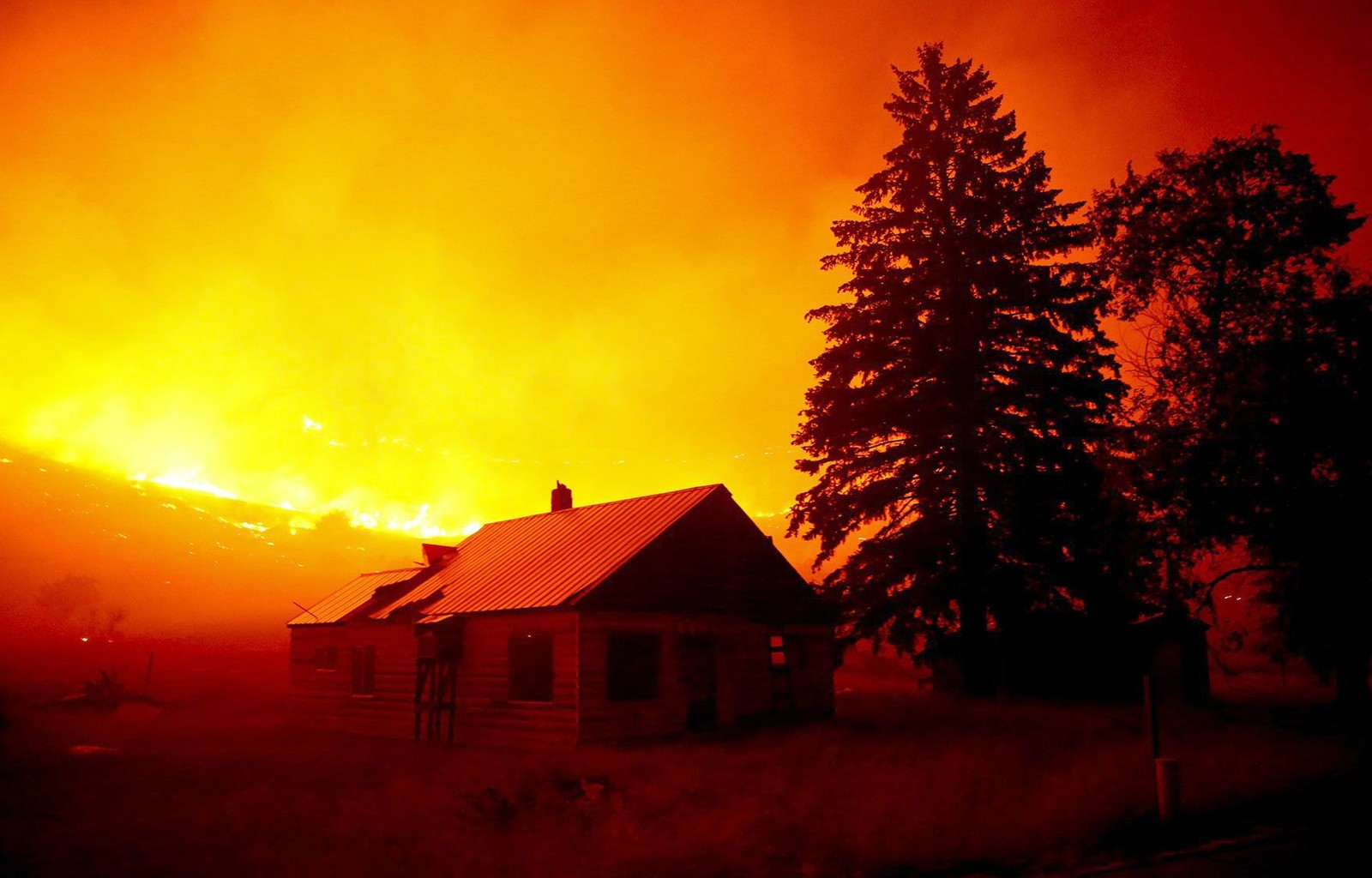 Flammer brer seg over Twisp River i Washington. Brannmannskaper kjemper mot flammene som truer flere byer i den nordre delen av staten.