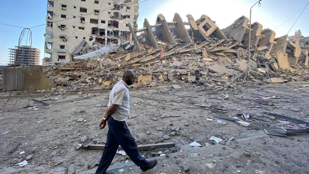 Mann går 12. mai forbi en boligblokk som ble ødelagt i Gaza by, etter israelske flyangrep.
