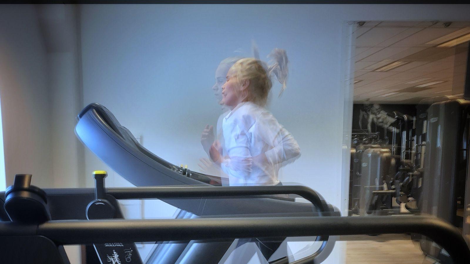 Sara løper på en tredemølle i et treningsstudio. Flere bilder er satt sammen slik at bildet ser litt uskarpt ut. Vi ser Sara fra siden. Hestehalen hopper, beina og armene viser at hun er i bevegelse.