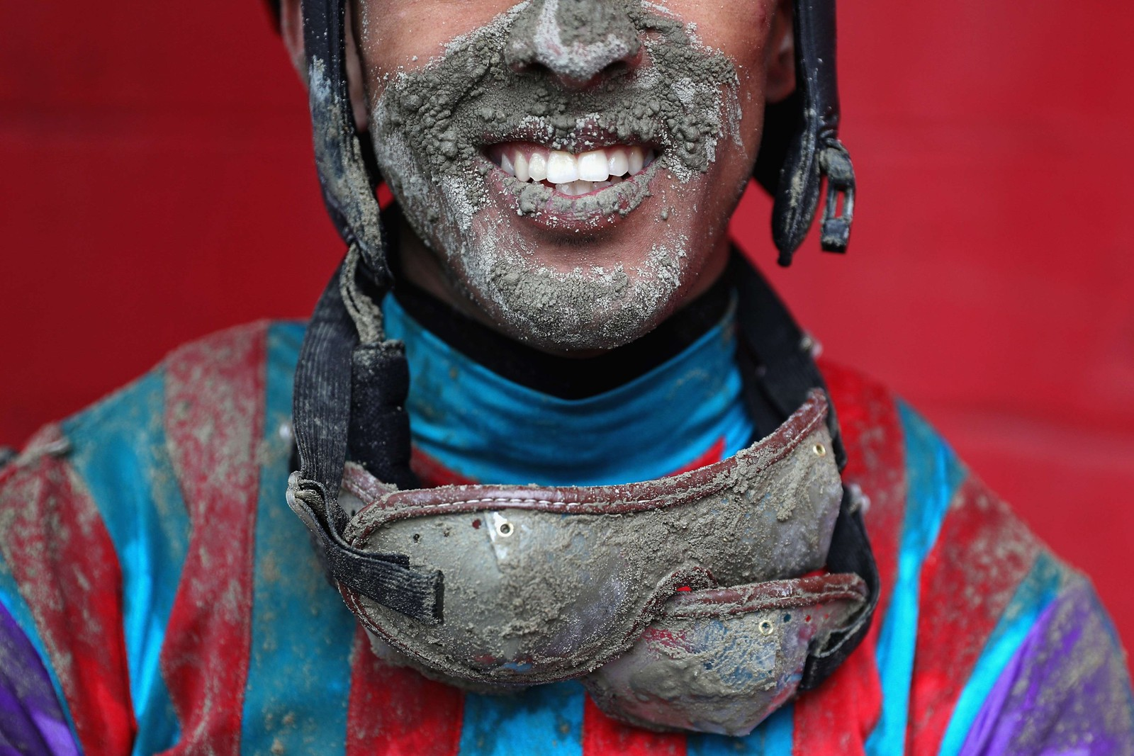 GJØRMEGLIS: Jockey Victor Carrasco gliste for fotografen etter et løp med hesten Never Stop Looking. Regnbyger gjorde travbanen Pimlico Race Course gjørmete.