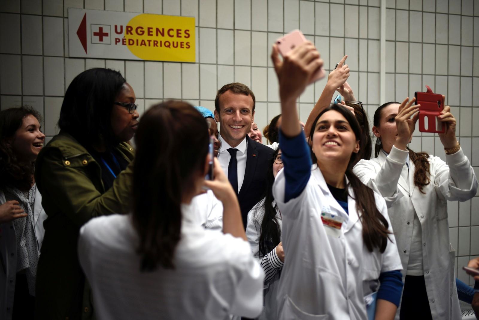 Frankrikes president Emmanuel Macron poserte for selfies med ansatte da han besøkte barnesykehuset Robert-Debre i Paris onsdag denne uken.