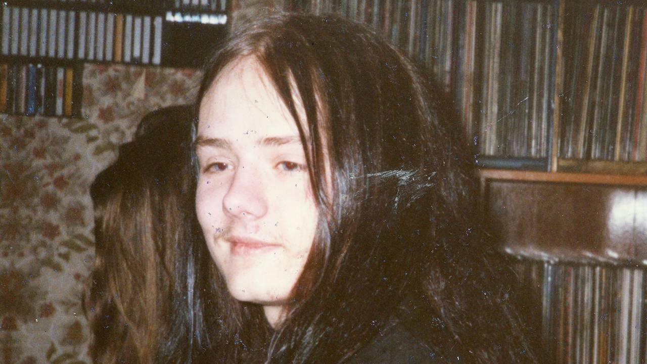 Øystein Aarseth som tenåring foran en hylle med vinylplater, med langt svart hår.