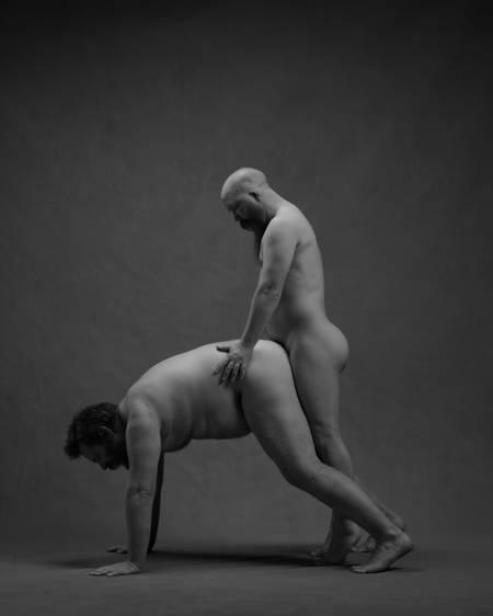 En naken mann står på alle fire på gulvet med rumpa opp. En naken mann står bak ham mellom bena hans med hendene på hoftene