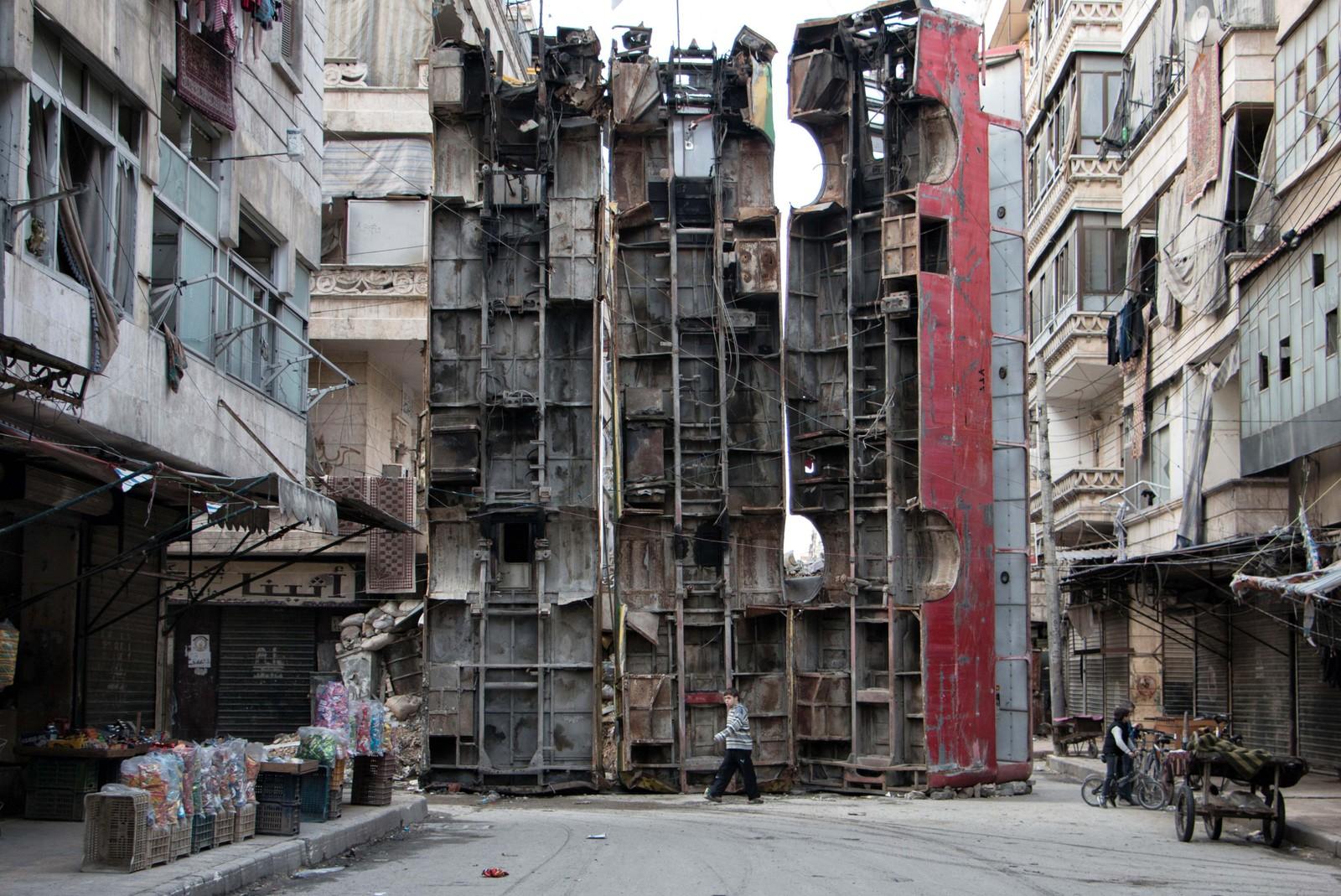 Tre busser plassert på høykant ble brukt som en barrikade i den syriske byen Aleppo i mars. Syrias mest folkerike by er hardt rammet av krigen i landet.