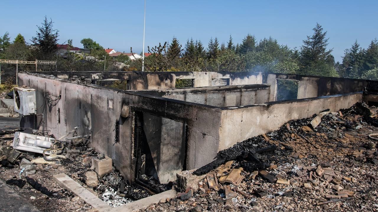 Ruiner av nedbrent hus etter skogbrannen i Øygarden, bare flaggstang og grunnmur står igjen