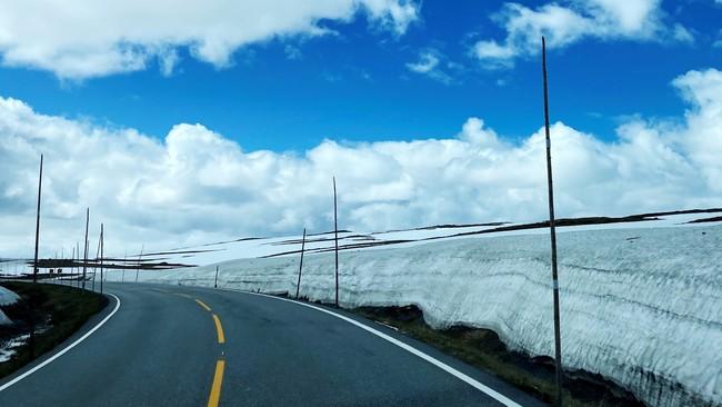 Hardngervidda med gule striper, hvit brøytekant og knallbrå himmel med noen skyer