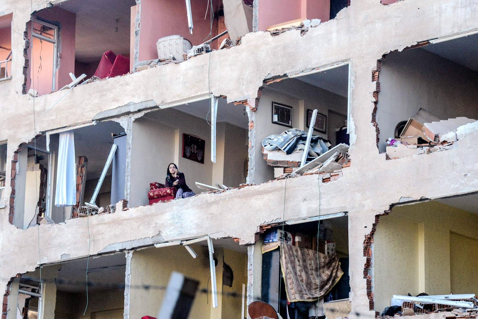 En kvinne sitter i den ødelagte leiligheten sin. En bilbombe forårsaket ødeleggelsene den fjerde november i den tyrkiske byen Diyarbakir.