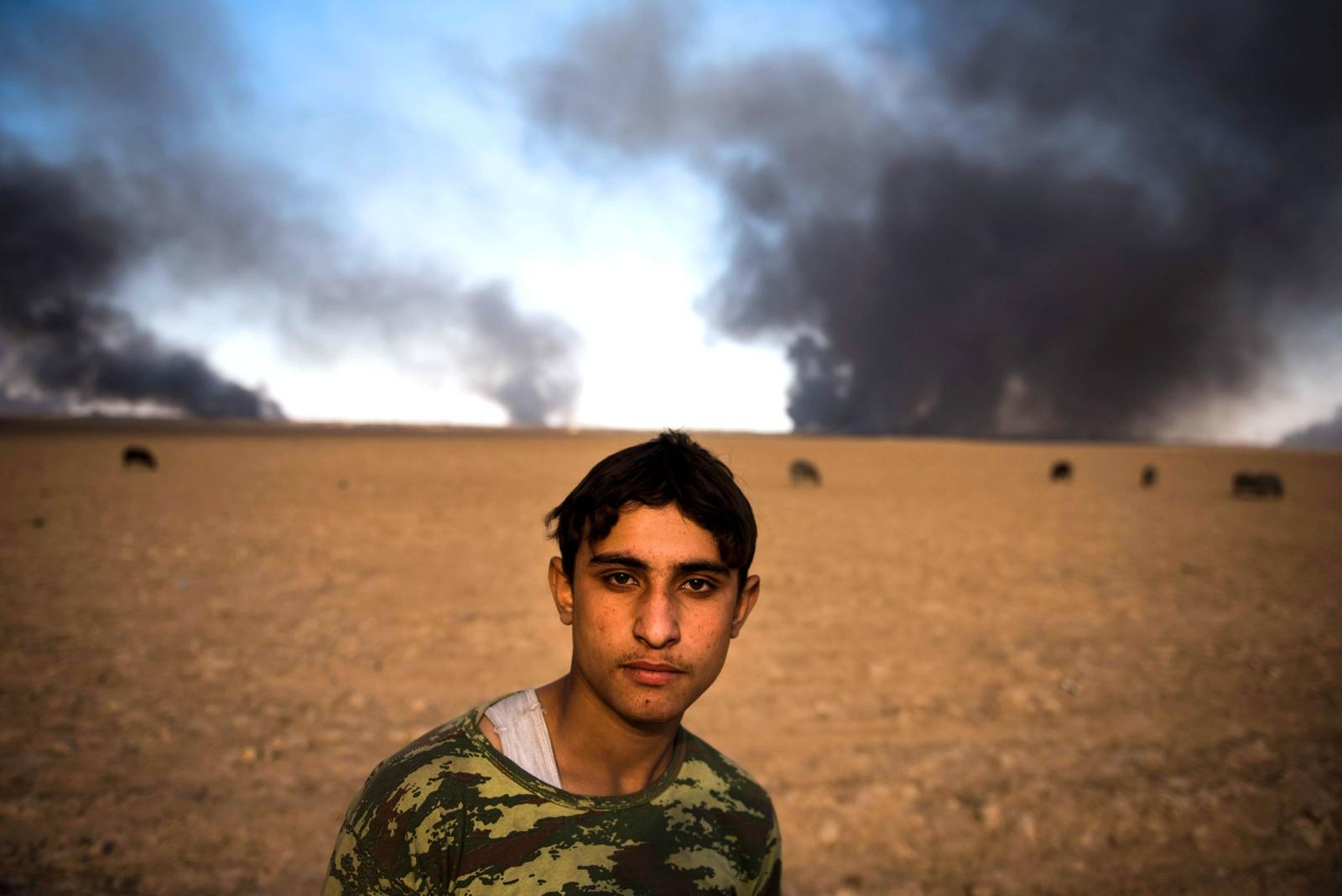 En gjeter passer på sauer. I bakgrunnen brenner oljebrønner som IS har satt i brann ved byen Qayara i Irak. Menneskene i området risikerer helseplager på grunn av den svarte røyken. Den er også årsaken til at sauene i bakgrunnen har blitt sorte.