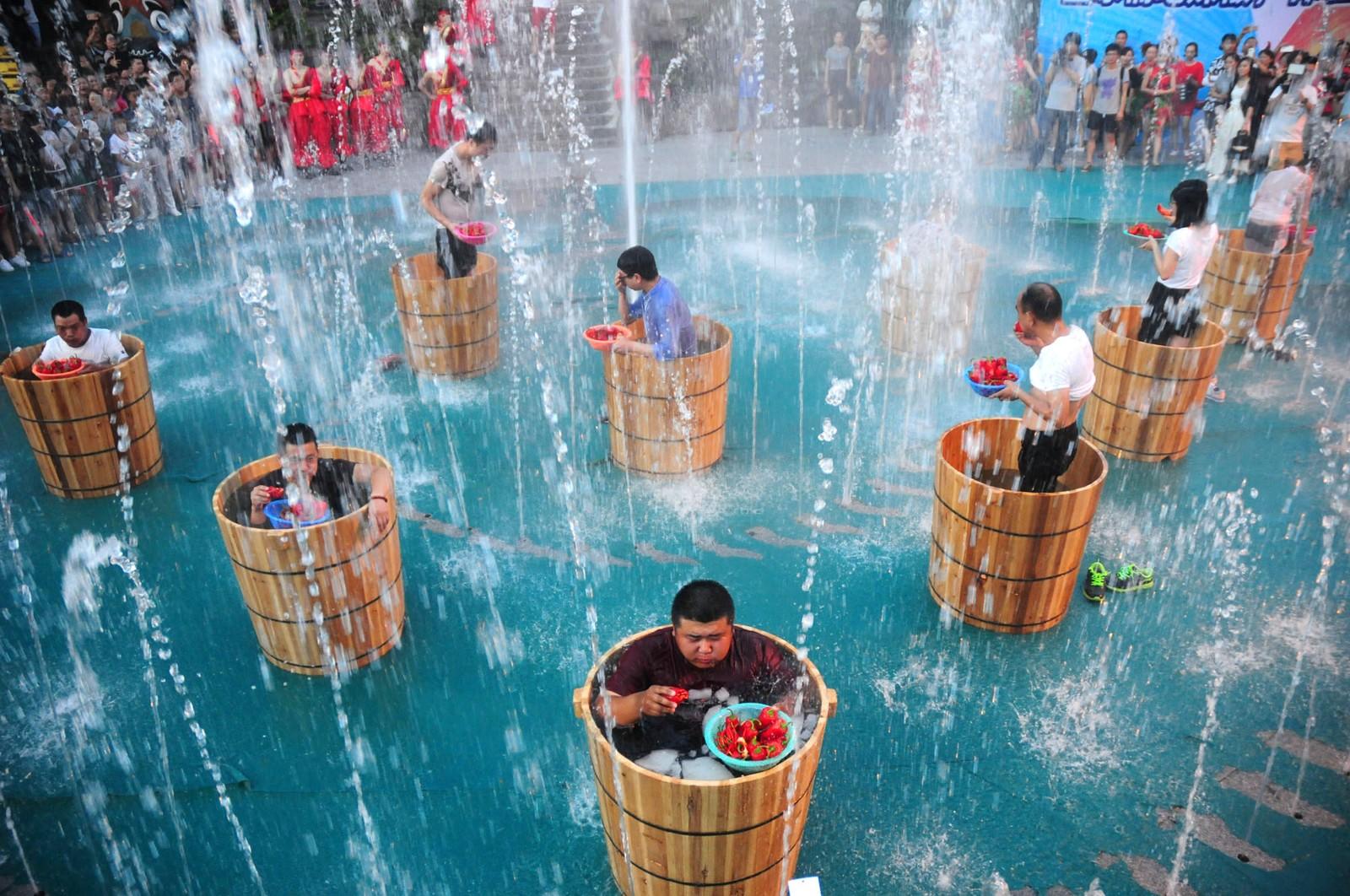 Ja, hvorfor ikke? Dette er deltakere i en chilispisekonkurranse som blir badet i iskaldt vann. Bildet er tatt den 20. juli i Hángzhōu i Kina.