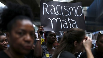 """BRAZIL-VIOLENCE/ A woman holds a sign that reads """"Racism kills"""" during a protest against the death of five youths in Rio de Janeiro"""
