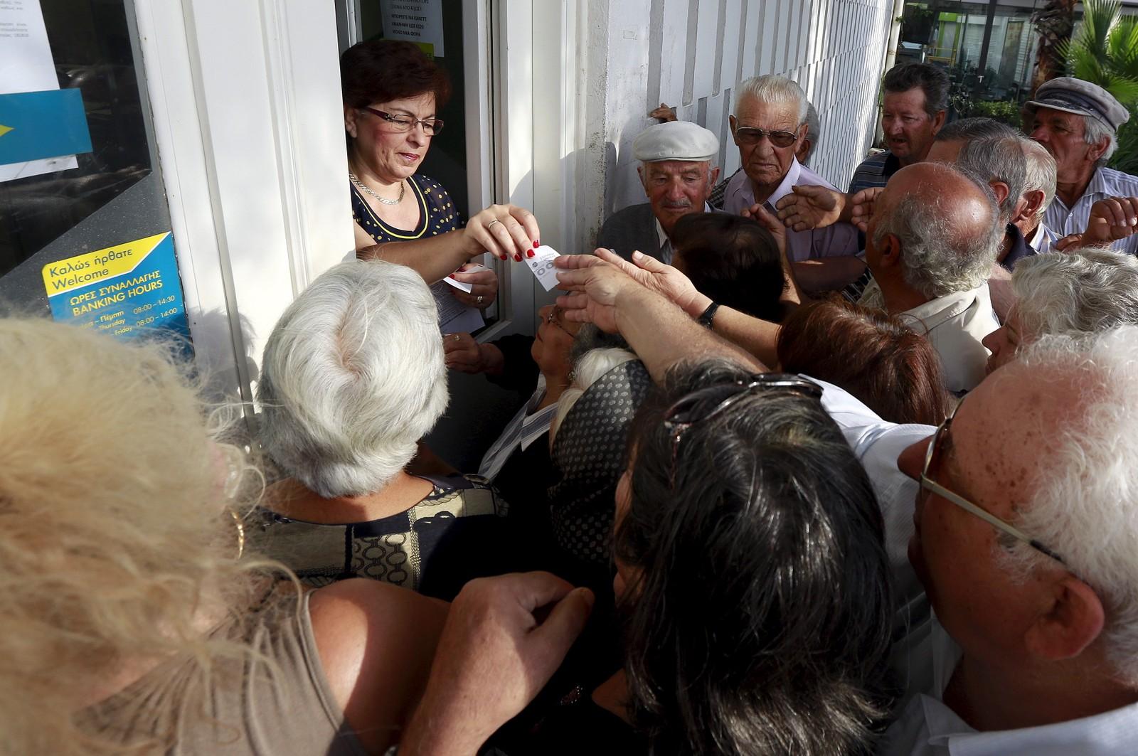 Pensjonister presser på for å få tak i en kølapp som deles ut ved en bankfilial på øya Santorini.