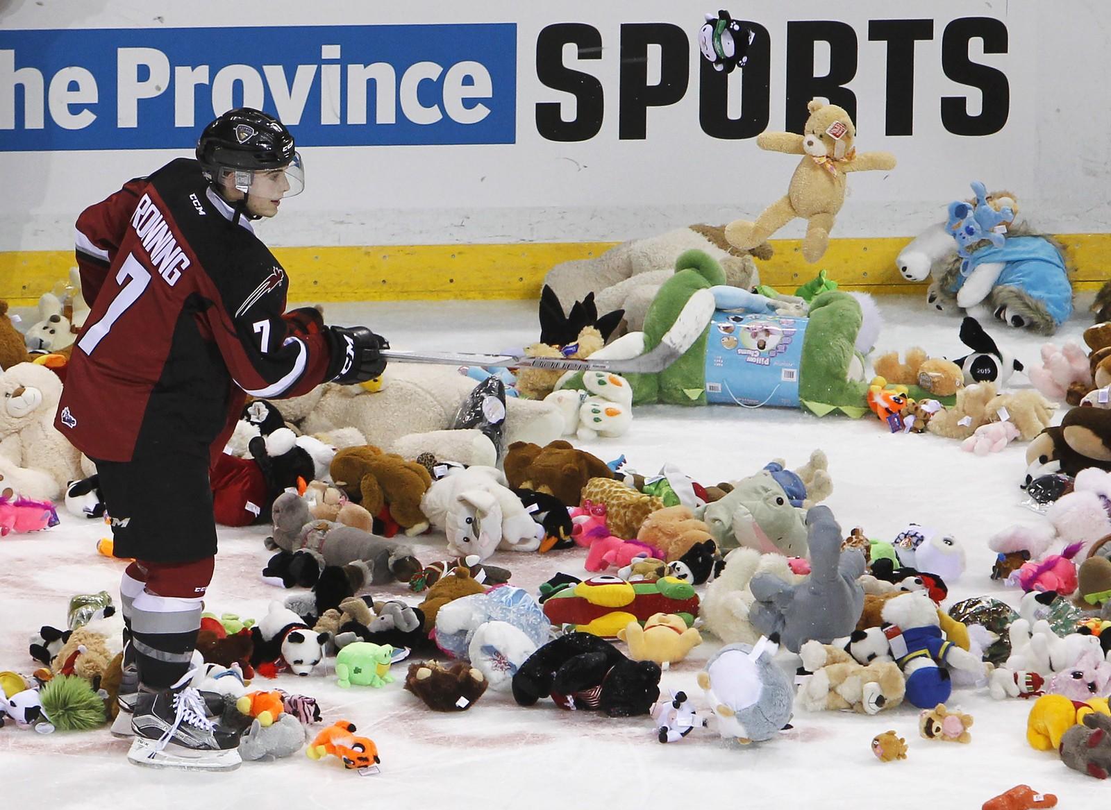 Vancouver Giants' Ty Ronning hjelper til med å fjerne alle bamsene som ble kastet inn på isen etter at han scoret mot Everett Silvertips i WHL-kampen 18. desember.