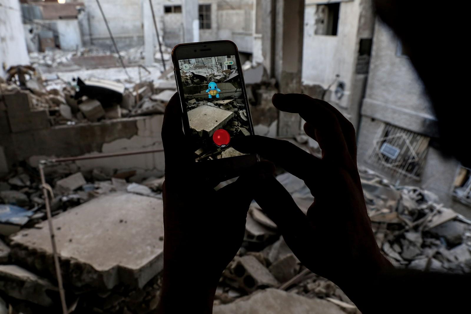 En syrisk spillentusiast spiller Pokemon Go på mobilen, og klarer å fange en Pokemon i ruinene av en bygning i Duma den 23. juli.