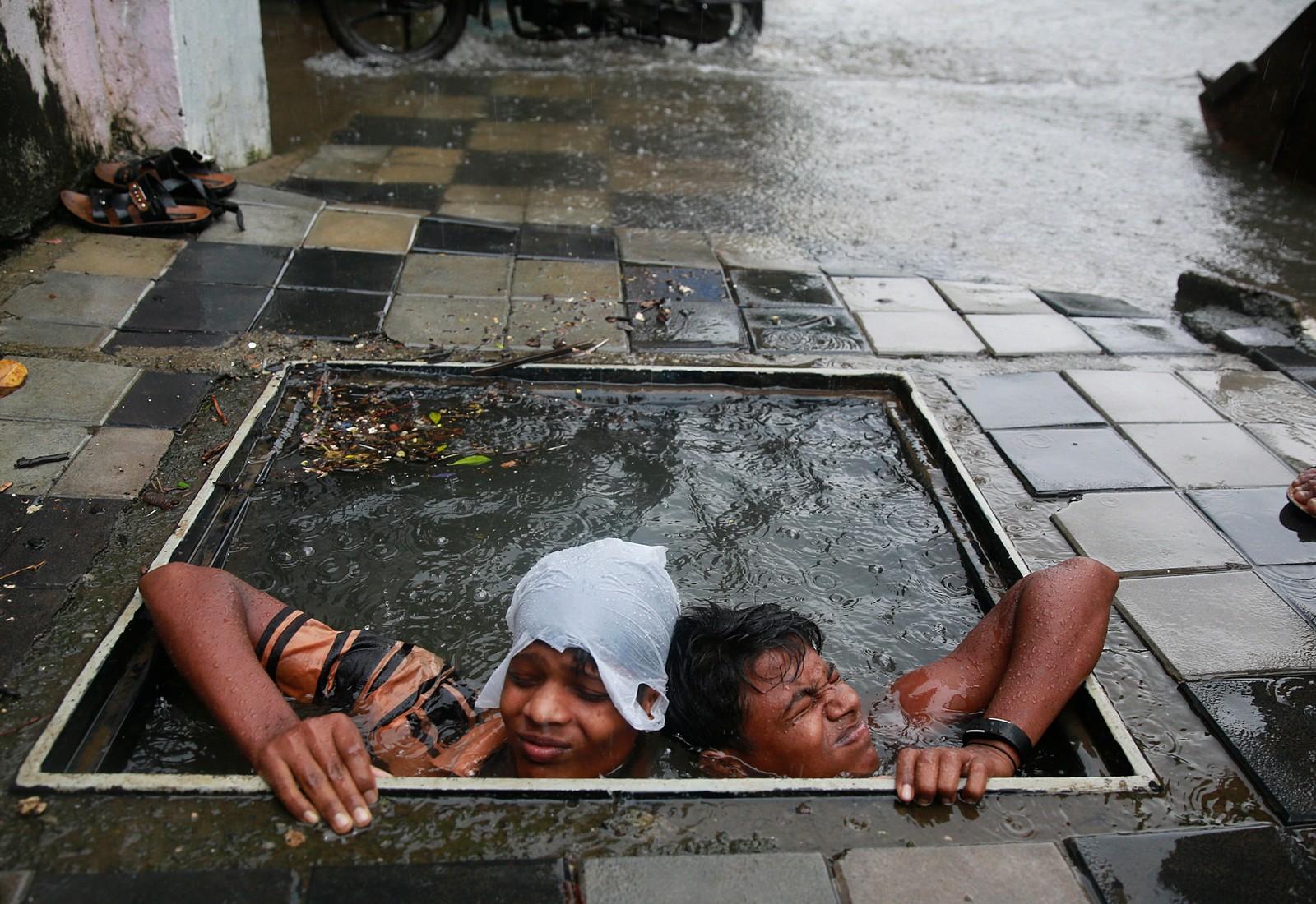 To menn prøver å finne et kumlokk for å unngå at fotgjengere i Mumbai, India mister fotfestet. Store mengder regn har ikke bare tatt med seg kumlokk, men også gått ut over togtrafikken, samt holdt skoler stengt.