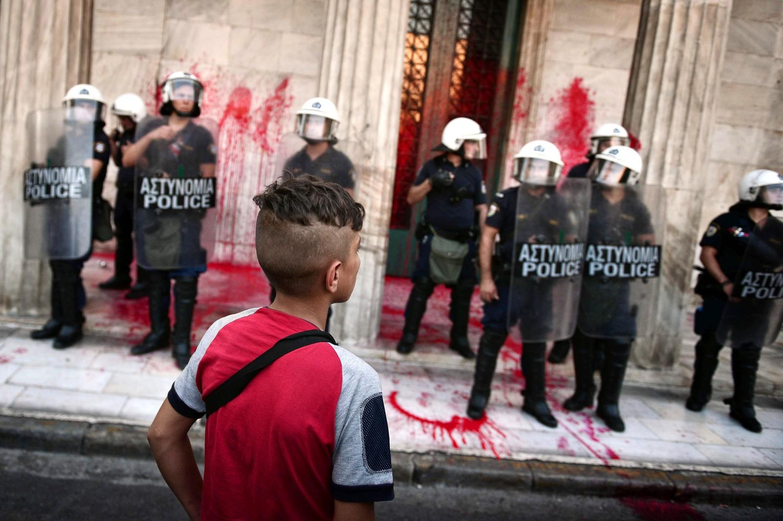 En gutt står foran en bygning som huser det politiske partiet SYRIZA (Koalisjonen av det radikale venstre), og ser på politifolk som passer på etter at demonstranter har kastet maling på fasaden den 29. august. Flere tusen flyktninger og støttespillere demonstrerte foran bygningen etter at flyktninger ble angrepet uken før. Demonstrantene krevde at flyktningene må beskyttes bedre.